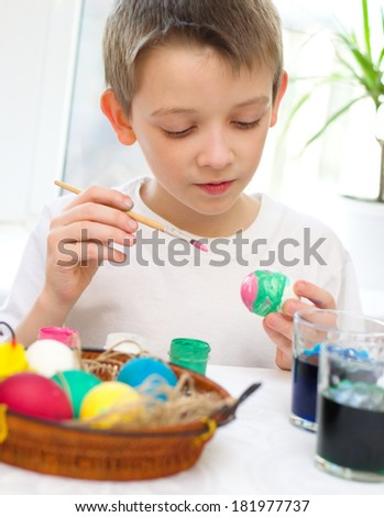 cute boy coloring eggs for Easter