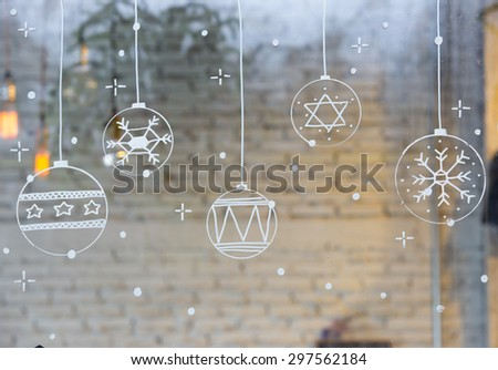 Cute boy drawing Christmas decorations on the glass - stock photo