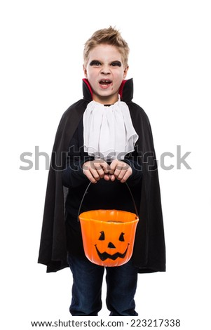 Cute boy dressed as a vampire for Halloween and holding a pumpkin basket. Studio portrait isolated over white background   - stock photo