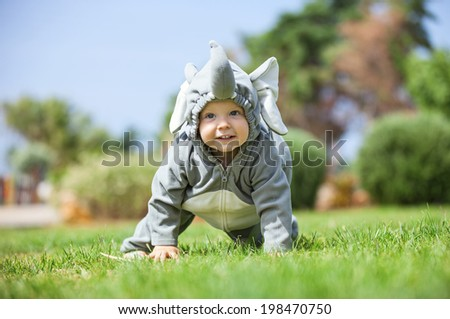 Cute boy dressed in elephant costume crawling on the lawn - stock photo