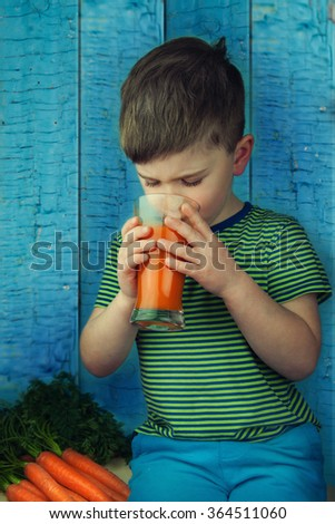 Cute boy drinking fresh-squeezed carrot juice