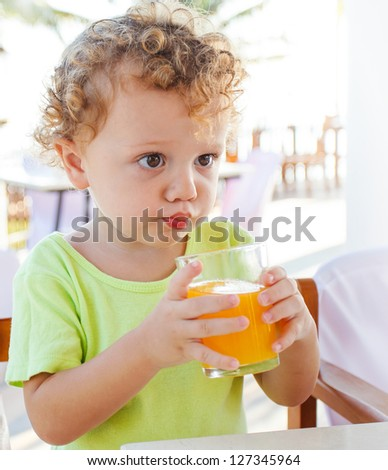 Cute boy drinking orange juice - stock photo