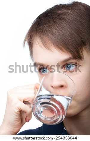 Cute boy drinking water on white background - stock photo