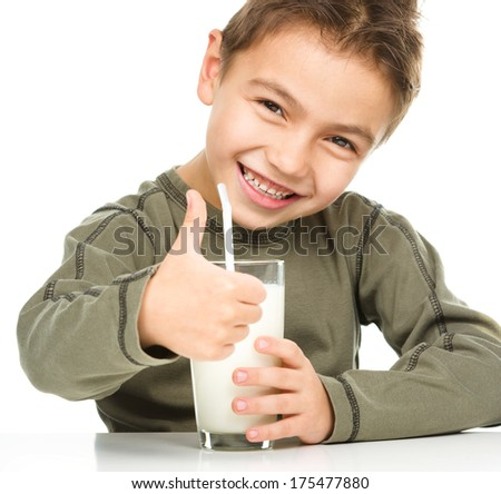 Cute boy drinks milk using a drinking straw while showing thumb up sign, isolated over white - stock photo