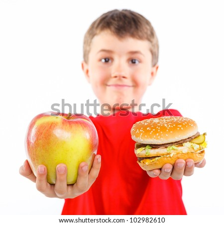 Cute boy eating a apple or hamburger. Focus on the apple and hamburger. Isolated on a white background - stock photo