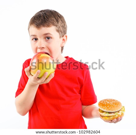 Cute boy eating a apple or hamburger. Isolated on a white background - stock photo