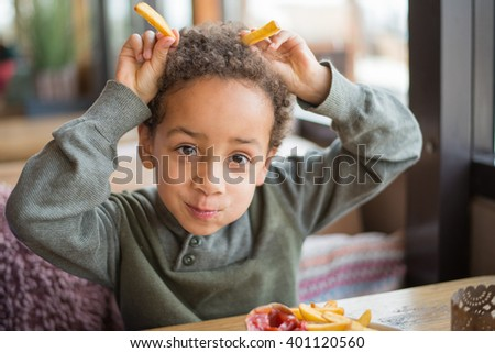 Cute boy eating french fries in restaurant - Funny faces - stock photo