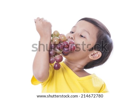 Cute boy eating grapes isolated on white  - stock photo