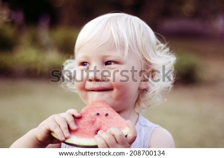 Cute boy eating watermelon - stock photo