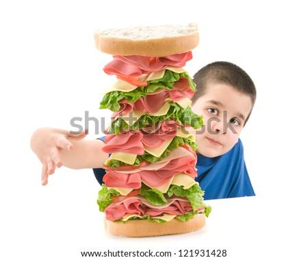 Cute boy enjoying big sandwich isolated on white - stock photo