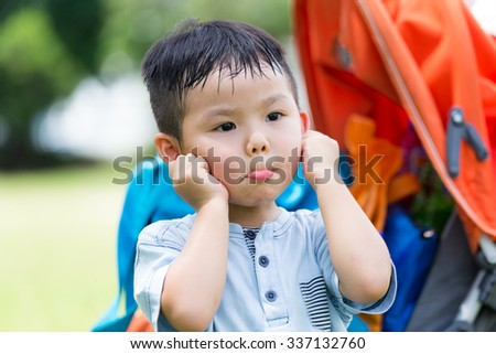 Cute boy feeling guilty with hand touch on his ear - stock photo