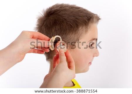 Cute boy getting his first hearing aid - stock photo