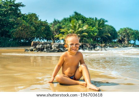 Cute boy have fun on tropical beach - stock photo