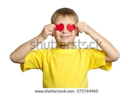 Cute boy holding a hearts shape on his eyes - stock photo