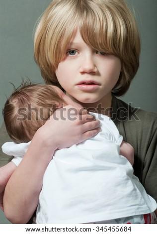 Cute boy holding a new born baby - stock photo