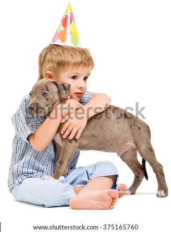 Cute boy hugging a pit bull puppy isolated on white background - stock photo