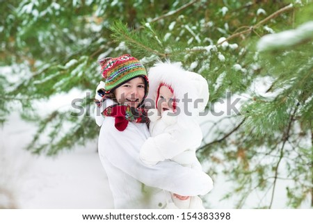 Cute boy hugging his baby sister in a beautiful winter park under a Christmas tree in snow both wearing warm white jackets and colorful knitted hats - stock photo