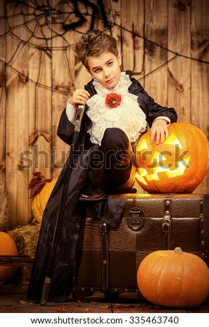 Cute boy in a costume of vampire posing in a wooden barn with pumpkins. Halloween holiday.