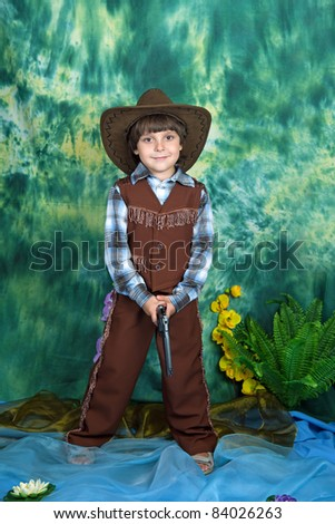 cute boy in a cowboy suit with a pistol on a green background