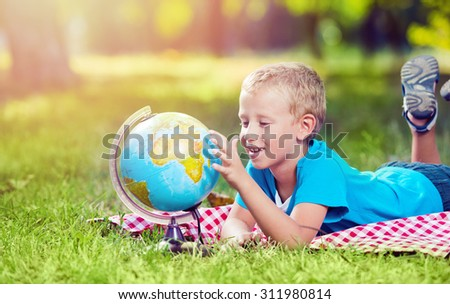 Cute boy in a park with a globe - stock photo