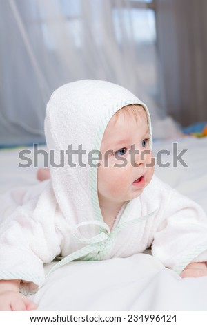 Cute boy in bathrobe with hood  lying on his belly  - stock photo