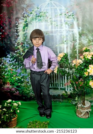 cute boy in business suit and purple shirt around flowering shrub