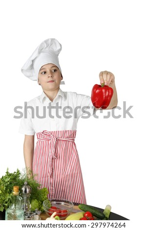 Cute boy in chef hat and apron astonishing stares on red sweet pepper in hand while cooking vegetables isolated on white background - stock photo