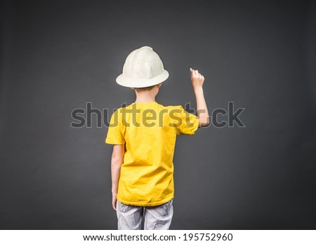 Cute boy in in helmet chalk something on the board. Back view of lovely boy drawing with a chalk. Concept of real estate and engineering. Copy space. - stock photo