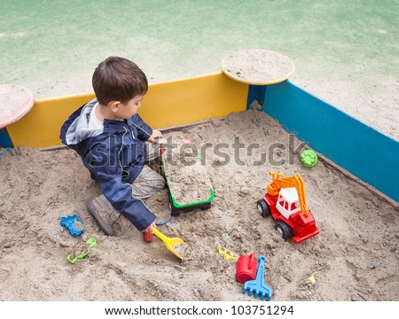 Cute boy in jacket playing in sandbox with a lot of sand toys - stock photo
