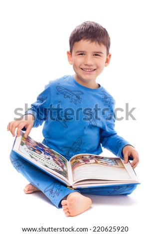 Cute boy in pajamas looking pictures in a book of fairy tales - stock photo