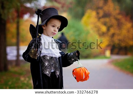 Cute boy in the park, wearing magician costume for Halloween, having fun - stock photo