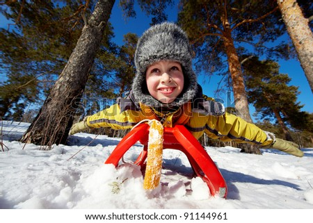 Cute boy in winterwear lying on sledge in park - stock photo
