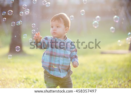 cute boy is catching bubble in the park, caucasian