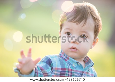 cute boy is catching bubble in the park, caucasian - stock photo