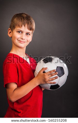 Cute boy is holding a football ball made of genuine leather  isolated on a black background. Soccer ball - stock photo