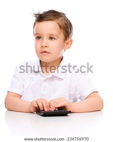 Cute boy is using calculator, isolated over white - stock photo