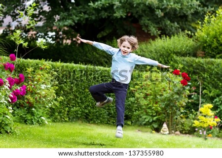Cute boy jumping in the garden - stock photo