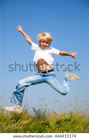 Cute boy jumping on summer meadow against blue sky