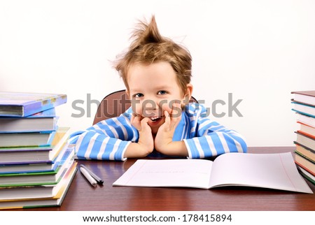 cute boy laughing sitting at the desk. many textbooks on the desk. light background.  horizontal