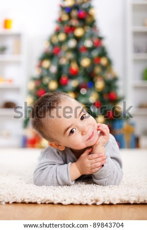 Cute boy laying in front of decorated christmas tree, prop his head - stock photo