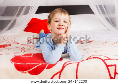 Cute boy laying on big bed