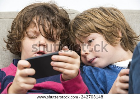 Cute boy looking at his younger sister who is playing a game on a smart phone on sofa - stock photo