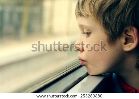Cute Boy looking through the window - stock photo