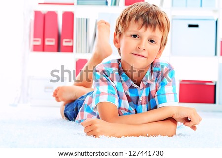 Cute boy lying on a floor at home. - stock photo