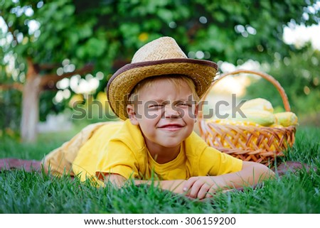 Cute boy lying on the blanket with a basket of corn