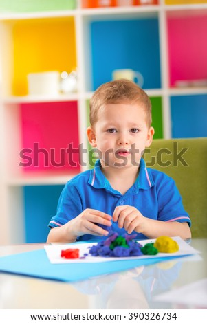 Cute boy making plasticine figures on the table