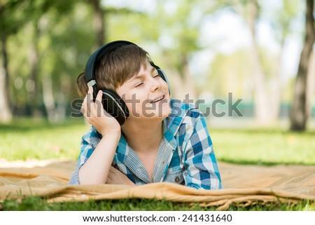Cute boy of school age in park wearing headphones - stock photo