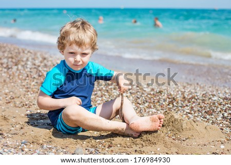 Cute boy of three years having fun with sand and stones on the beach in summer during holiday vacations
