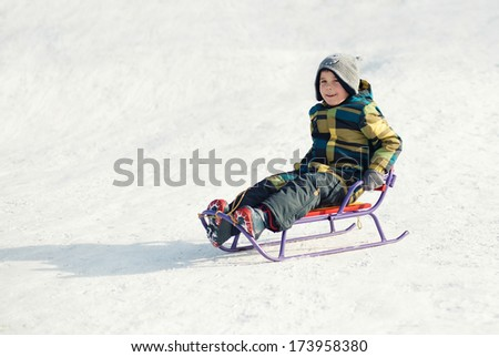 cute Boy On A Sled In The Snow