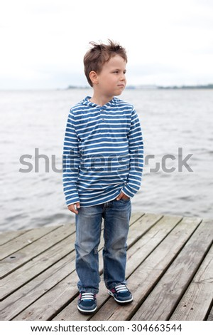 Cute boy on the north sea, wearing stripped t shirt   - stock photo